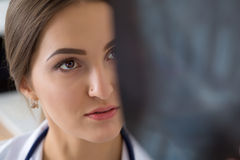 Young female medical doctor or intern looking at lungs x-ray ima. Young female medical doctor or intern looking at lungs x ray image standing at her office Stock Photos