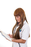Young female medical doctor with stethoscope reading book Stock Photos