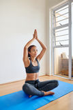 Young female meditating in a yoga position. Fitness woman meditating, practicing yoga at home Stock Photo
