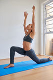 Young female meditating in a yoga position. Fitness woman meditating, practicing yoga at home Royalty Free Stock Image