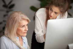 Young female mentor teaching senior woman colleague explaining c royalty free stock photography