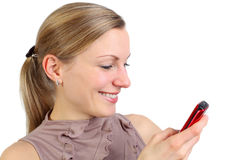 Young female messaging. Young blonde holding her mobile phone and messaging (isolated on white Royalty Free Stock Photos
