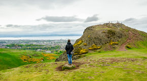 Young female model admiring Edinburgh landscape from the top of. The Arthur's seat. Scotland, UK Royalty Free Stock Photo