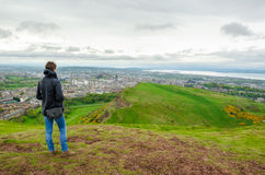 Young female model admiring Edinburgh landscape from the top of. The Arthur's seat. Scotland, UK Stock Photography