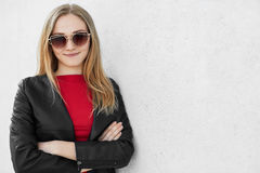 Young female model with blonde hair wearing sunglasses, red sweater and leather jacket standing crossed-hands having convinced loo. K posing against white Royalty Free Stock Photo