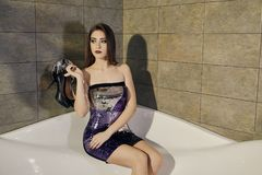 Young female model in the cocktail dress with brunette hair posing at the bath whith pair of shoes stock photos