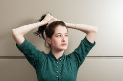 Young female model grasping her hair Royalty Free Stock Photography