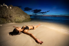 Young female model lying in water on golden sunset Stock Photography
