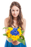 Young female model offering a bouquet of flowers. Young female model with long hair offering a bouquet of flowers Stock Photo