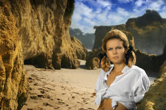 Young female model on rocky beach. Horizontal portrait of beautiful blond girl on a rocky beach Stock Photography