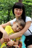 Young female model smiling while looking at the camera, sitting on a bench in the park with her little son. stock photos