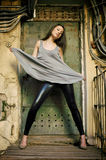 Young female model standing before rusty door Royalty Free Stock Image