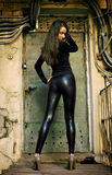 Young female model standing before rusty door Royalty Free Stock Images