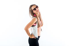 Young female model standing sideways, bending her body, putting arm on hip, wearing sunglasses and bright accessories. Royalty Free Stock Images