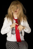 Young female model straightening her tie with messy hair Royalty Free Stock Photo