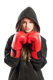Young female model wearing red boxing gloves and black hoodie Stock Image
