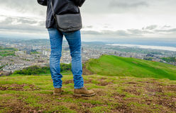 Young female model wearing skinny blue jeans and b. Rown suede boots admiring Edinburgh landscape from the top of the Arthurs seat. Scotland, UK Royalty Free Stock Image