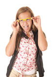 Young female model with yellow glasses sticking her tongue out Stock Image
