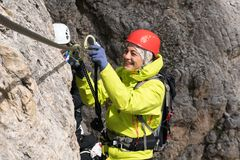 Young female mountain climber on a Via Ferrata in the Dolomites in Alta Badia clicking carabiners in the cable. For safety and smiling stock photo