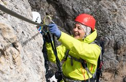 Young female mountain climber on a Via Ferrata in the Dolomites in Alta Badia clicking carabiners in the cable. For safety and smiling royalty free stock photos