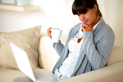 Young female with a mug browsing the internet Royalty Free Stock Photography