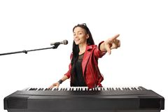 Young female musician playing a digital piano, singing on a microphone and pointing. Isolated on white background royalty free stock photo