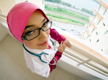 Young female Muslim doctor. A young female doctor wearing a white coat with a stethoscope around her neck Royalty Free Stock Image