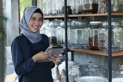 Entrepreneurs check stock on coffee in a jar shelf using tablet pc, businessman checking storage stock images