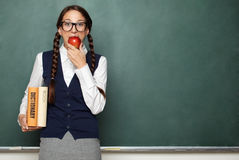 Young female nerd with books and apple. In front of blackboard Stock Photos