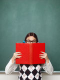 Young female nerd holding book stock photography