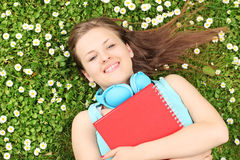Young female with notebook listening music and lying on a grass Royalty Free Stock Photography