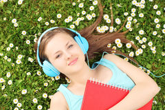 Young female with notebook listening music and lying on a grass Royalty Free Stock Image