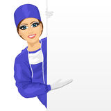 Young female nurse in blue scrub suit presenting empty banner Royalty Free Stock Photos