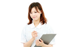 Young female nurse with clipboard Stock Images