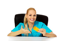 Young female nurse or doctor sitting behind the desk and holding  packet of pills Stock Photo