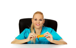 Young female nurse or doctor sitting behind the desk and holding  packet of pills Stock Image