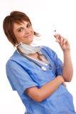 Young female nurse holding filled syringe. Young smiling female nurse holding filled syringe Royalty Free Stock Image