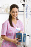 Young female nurse holding IV stand in hospital ward, smiling, portrait Royalty Free Stock Images