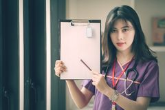 Young female nurse holding pencil and showing her clipboard Stock Image