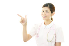 Young female nurse pointing. Portrait of an Asian female nurse Royalty Free Stock Images