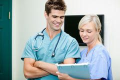 Young Female Nurse Showing Clipboard To Male Vet. Young female nurse showing clipboard to smiling male vet at clinic Royalty Free Stock Image