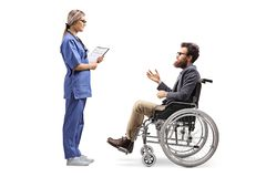 Young female nurse talking to a bearded man in a wheelchair stock photography