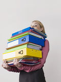 Young Female Office Worker Carrying Heavy Binders Stock Photo
