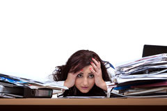 Young female office worker. Helplessly looking at the pile of papers with place for text Royalty Free Stock Photography