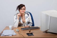 Young female office worker. Sitting behind a desk at a computer Stock Photos