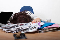 Young female office worker. Sleep at a desk with a pile of papers Stock Photo