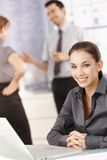 Young female office worker smiling in office Royalty Free Stock Photography