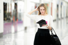 Young female out of money checking her purse in disbelief. Troubled young woman looking perplexed into her wallet, spending money, limited budget, finance Royalty Free Stock Photo
