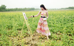 Young female painter. Young female artist painting in rape field Royalty Free Stock Images