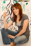Young female painter or artist. Casual portrait of a woman artist sitting in front of her contemporary graffiti type painting Stock Photos